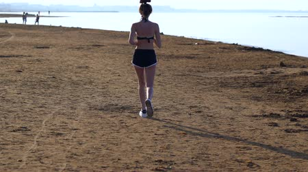 verhuizen : Fit young woman jogging along a sandy beach