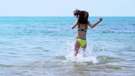 brodění : Young woman in bikini running into the sea Dostupné videozáznamy