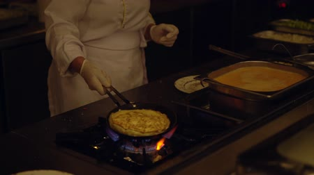 omlet : Chef preparing an egg omelette over a burner