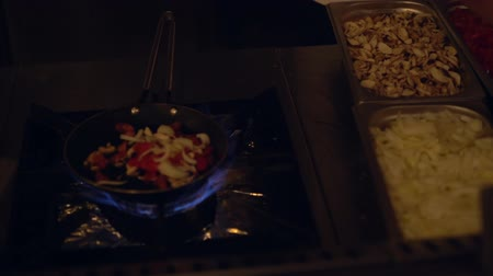 gas burner flame : Chef selecting fresh ingredients into a pan