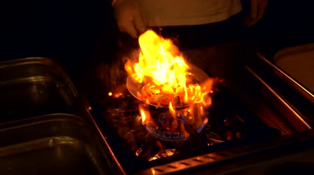 coals : Close up of chef flipping a flaming hot frying pan