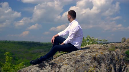 склон холма : Young man sitting overlooking a wooded valley