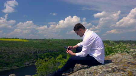 engrossed : Young man sitting on a rock using a mobile