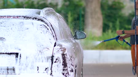 hosing : Young man hosing down his car covered in soap suds