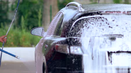 mülkiyet : Young man hosing down a soapy car Stok Video