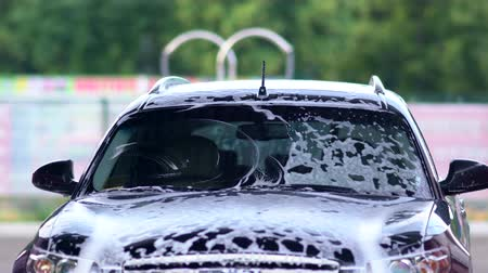 kaput : Young man washing his windscreen with soap