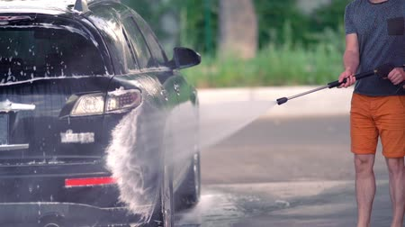 squirting : Young man hosing the shampoo off his car