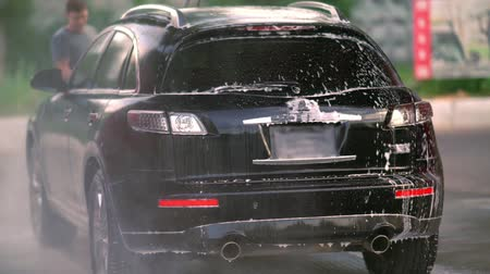 zaparkoval : Black saloon car being washed at a car wash Dostupné videozáznamy