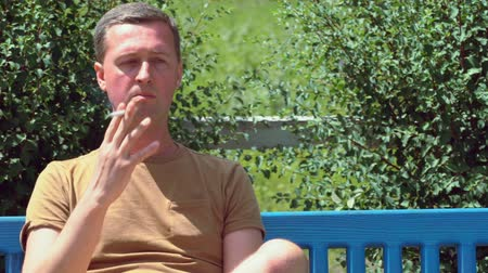 puffing : Man sitting on a park bench smoking