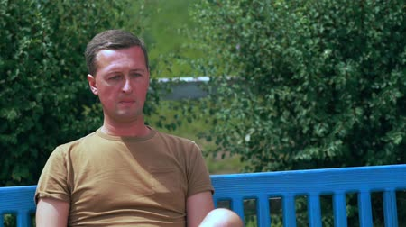 addiktív : Man relaxing enjoying a cigarette on a park bench