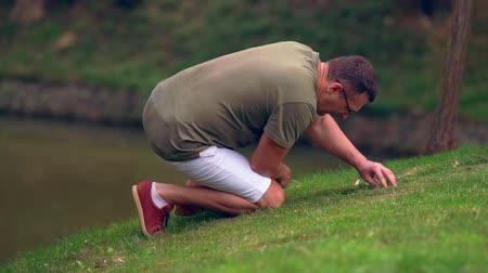 naturalist : Man searching in short grass on the bank of a pond