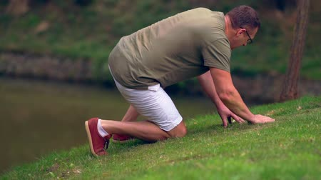 naturalist : Man searching the grassy bank of a pond Stock Footage