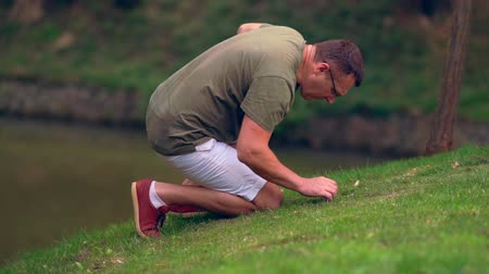 naturalist : Man searching in the grass alongside a lake