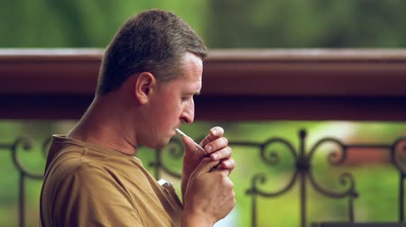 puffing : Man sitting smoking a cigarette outdoors