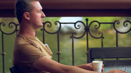 puffing : Man smoking and drinking coffee at a restaurant Stock Footage