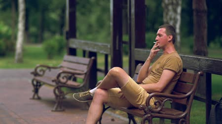 puffing : Man seated on a park bench smoking a cigarette