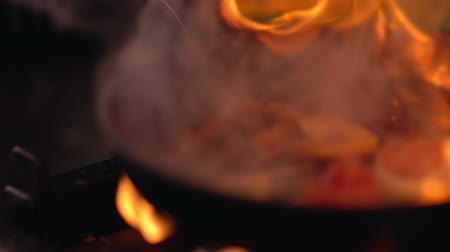 Chef flaming food over a hot fire in a pan Stock Footage
