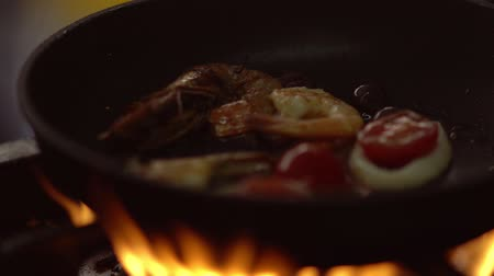 Chef heating seafood in a pan over open flames