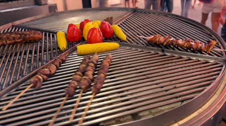 Rotating grill with roasting vegetables and kebabs