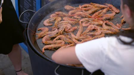 Woman cooking queen pink prawns on a griddle