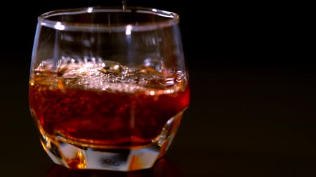 amadurecida : Pouring brandy or whiskey into a glass with ice