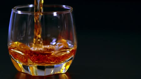 bourbon whisky : Pouring neat brandy or whiskey into a glass Stock mozgókép