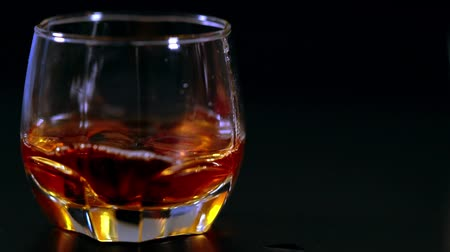 bourbon whisky : Dropping ice cubes into a tot of whiskey