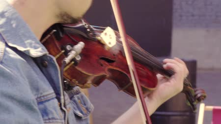 Man playing a violin outdoors in a close up view Wideo