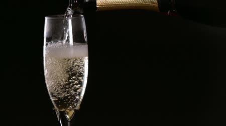 Slowly pouring a glass of sparkling champagne