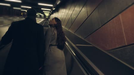 Young couple riding up on an escalator together Wideo