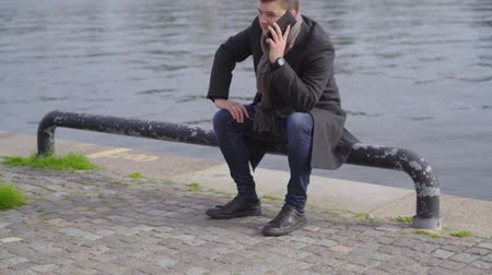 Young man sitting on a bollard using a mobile Wideo