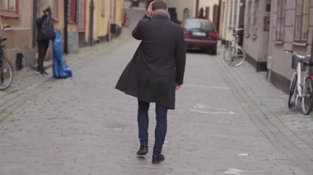 Young man in overcoat turning an walking away