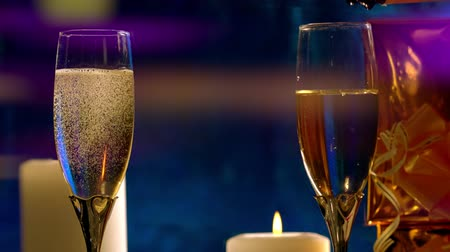 Pouring two flutes of champagne by candlelight Stock Footage