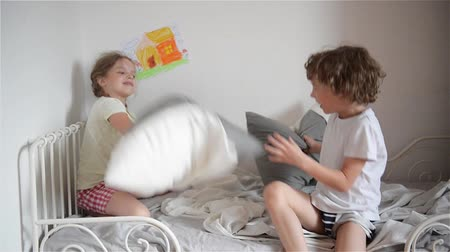 hádka : The brother and the sister have arranged fight by pillows on a bed in a bedroom. Dostupné videozáznamy