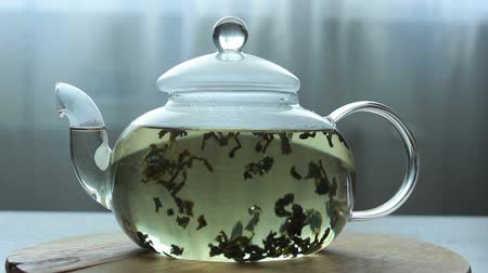 brew tea : video of Process of brewing green Chinese tea in a glass teapot on wooden background Stock Footage