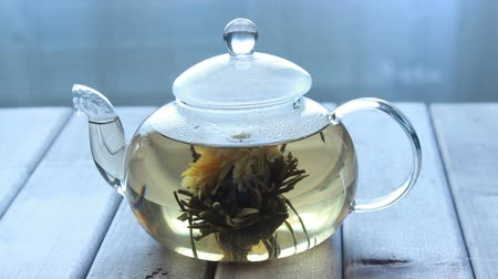 brew tea : video of a glass tea pot with Flower Chinese tea on light wooden background in front of the window.