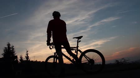 bisiklete binme : Cyclist arrives and takes a break at sunset Stok Video