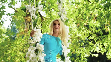 Attractive blonde on a swing made of flowers