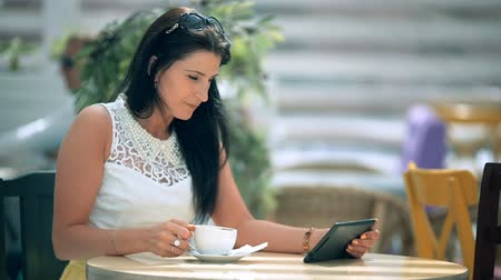 diner : Happy young woman drinking coffee  tea and using tablet in a coffee shop
