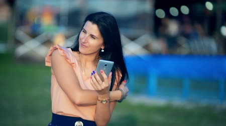 колледж : Young women in a park is holding a smartphone and typing