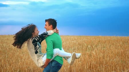abraços : Happy сouple having fun outdoors in wheat field over sunset. Laughing Joyful Family together. Slow motion
