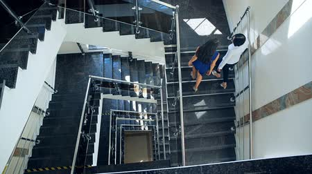trabalho em equipe : Business couple walking up stairs together. The view from the top Vídeos