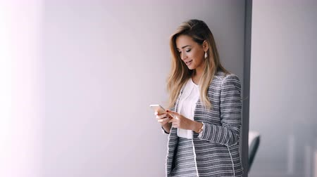 продавщица : Businesswoman sending message with smartphone in office