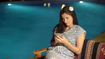 КПК : Happy girl using a smartphone, typing near swimming pool in the evening.