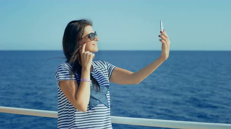 capitão : Attractive young woman on yacht taking a selfie photo