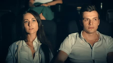 néző : Young man and woman watch movie, embrace in cinema theater