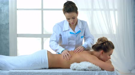 masszírozó : Woman having massage of body in the spa salon. Stock mozgókép