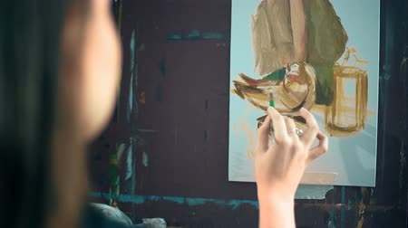 шедевр : Artist paints picture on canvas with oil paints in her workshop