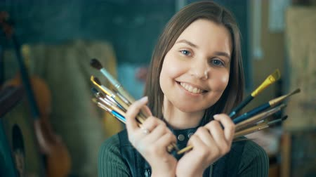 relance : Young smiling women painter with many brushes looking at the camera
