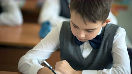 alfabetização : School boy writing on his notebook in the classroom Stock Footage
